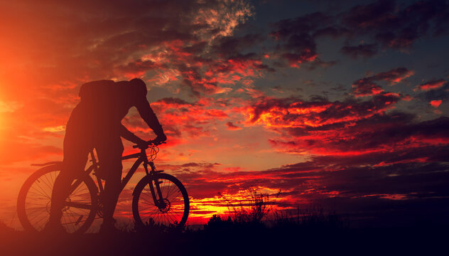 cyclist with a bicycle, in the background fiery sunset.