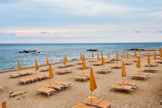 Beautiful empty beach with yellow sand with empty sun beds and orange umbrellas. Sunset sky. Vacation at the sea.