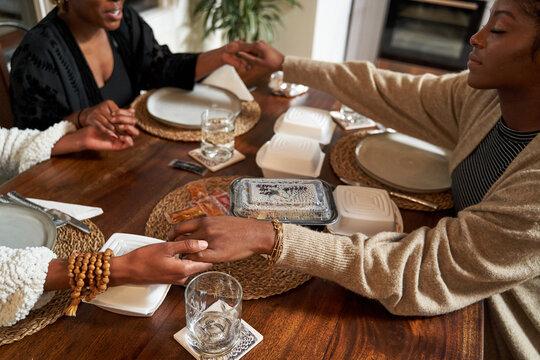 Black female friends praying blessing food, togetherness