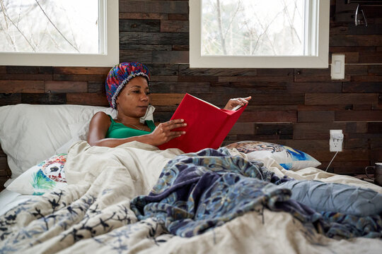 African American woman reading book in bed