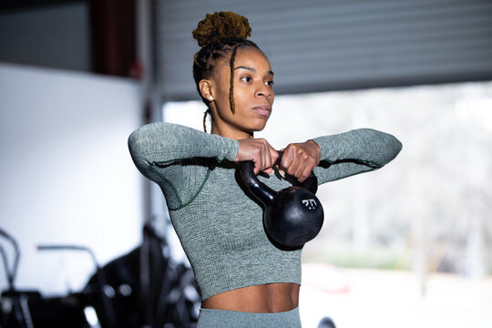 Black woman does fitness workout, kettlebell upright row