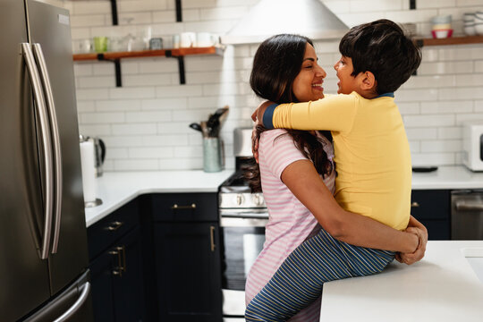 Smiling Indian mom embracing son at home in kitchen