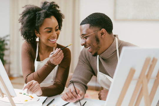 Black couple has fun painting and laughing during date night, paint and craft DIY