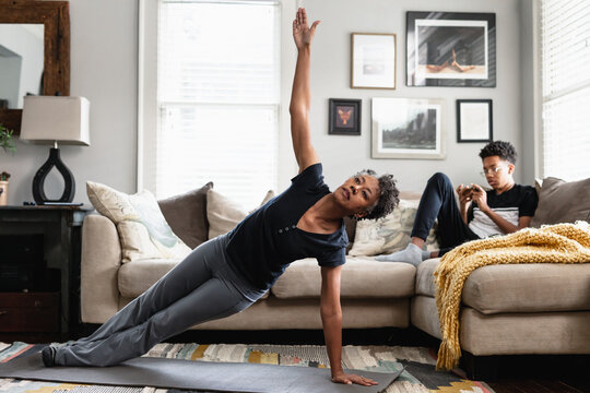 Black mom working out in family room, teenage son on phone in background, side plank exercise