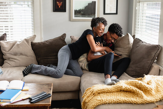 Black mother and son laughing together on couch, loving moment