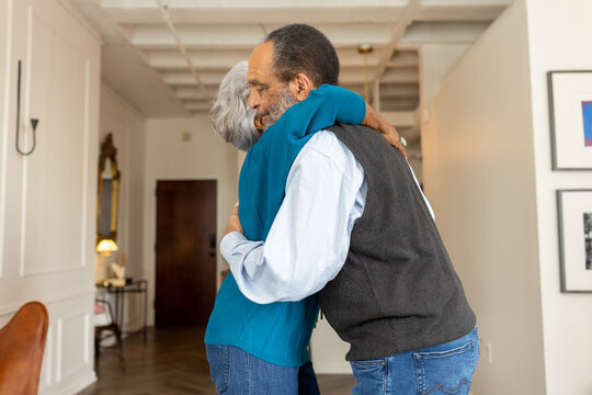Black senior couple embracing, celebrating their love with rose flowers at home
