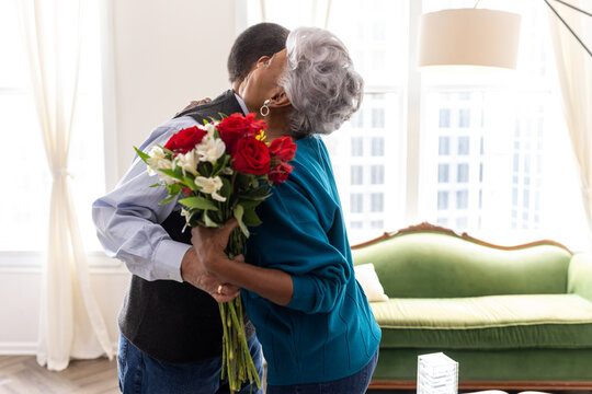 Senior couple celebrating wedding anniversary with roses at home, love connection