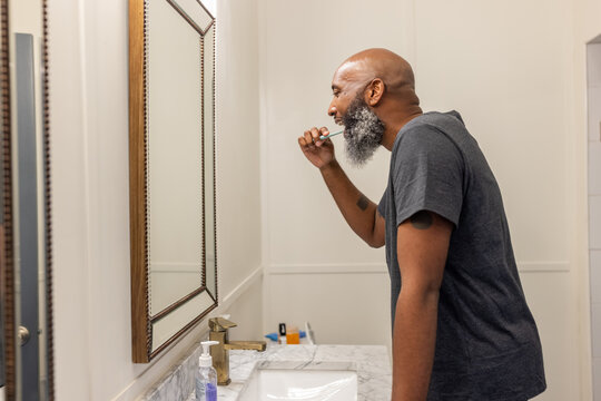 Black man with gray beard brushes teeth in bathroom at home