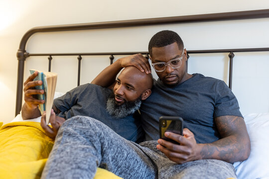Black couple cuddling in bed at home, LGBTQ pride love connection