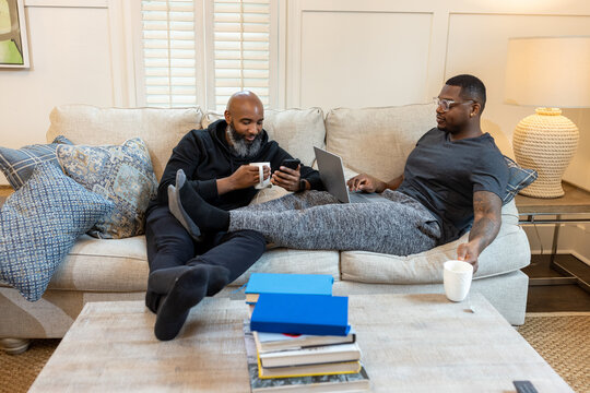 Black gay couple at home in living room, loving relationship