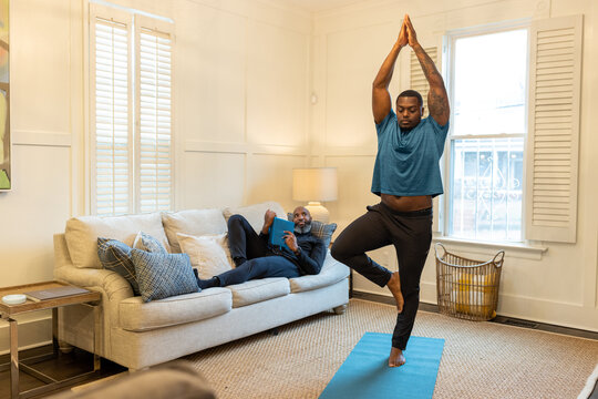 Man watches his partner doing yoga, tree pose
