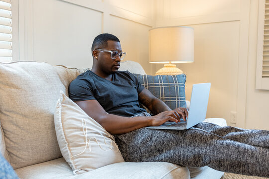 African American man working from home on laptop in living room, video chat conference call