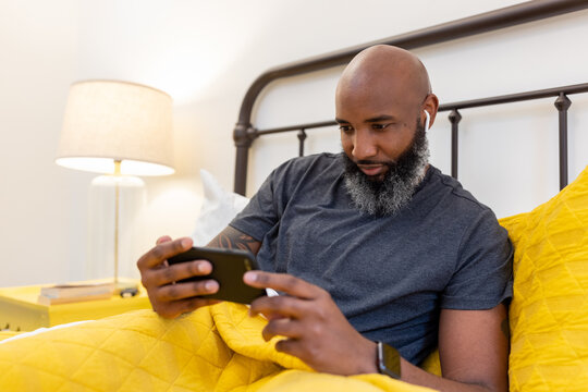 Black man with gray beard on phone in bed at home
