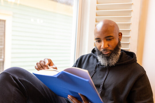 Black man enjoys reading book at home in nook, cozy and comfortable