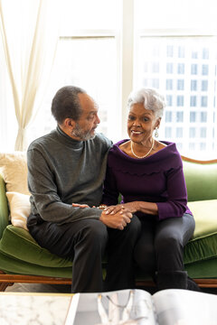 Senior Black couple sitting on couch at home