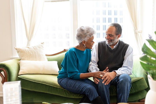 Senior African American couple sitting, smiling, on couch, connections