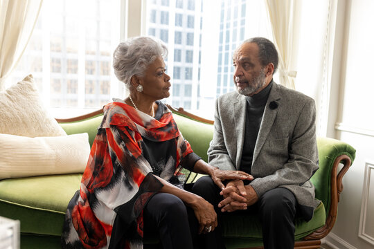Black senior couple embracing, celebrating their love, holding hands at home