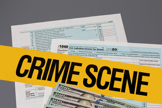 1040 individual income tax return with crime scene tape. Identity theft, tax fraud and cybercrime concept