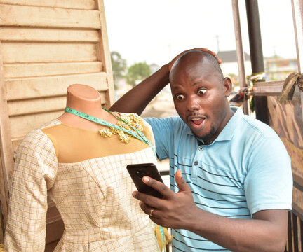 A Nigerian tailor surprised as he stare into the phone in his hand