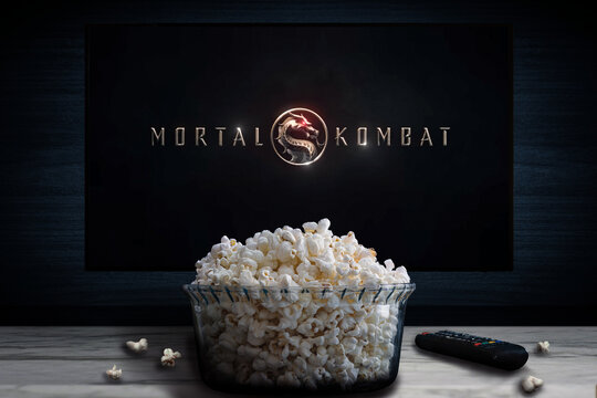 """Cali, Colombia - March 1 2021: """"Mortal Kombat"""" movie logo on tv screen behind a bowl of popcorn and a remote control."""