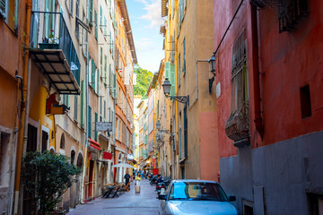 One of the many narrow alleys with high walls of apartments and shops through Old Town Vieux Nice, France, on the French Riviera.