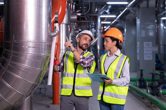 Industry engineer worker wearing safety uniform under checking the industry cooling tower air conditioner is water cooling tower air chiller HVAC of large industrial building to control air system.