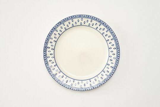 hermoso plato blanco con figuras, estilo casa de la abuela, fondo blanco, foto clave alta, objetos de cocina del hogar, marco azul