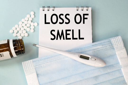The inscription loss of smell on a notebook that lies on a blue background with a bottle and scattered pills and a medical mask and a thermometer. Medical concept