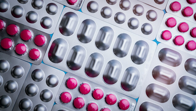 Pink tablets in blister pack and silver aluminium foil pack for capsule and tablets pills in pharmaceutical industry. Pharmaceutical package manufacturing. Top view of round tablets pills. Pharmacy.