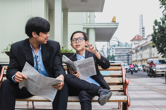 Two brothers wearing blue shirt and black suit sitting on the bench while holding newspaper and joking