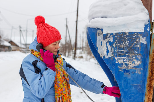 An elderly woman calling from a pay phone in the village in winter.
