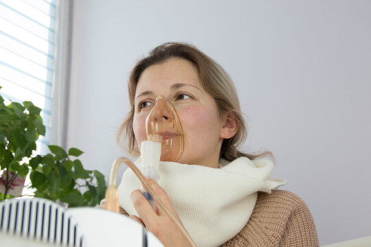 portrait of a young woman inhaling medicines for bronchitis and asthma at home