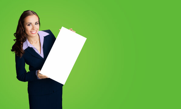 Happy smiling woman in black confident suit showing blank white signboard. Business and advertising concept. Copy space empty place for some text. Green color background..