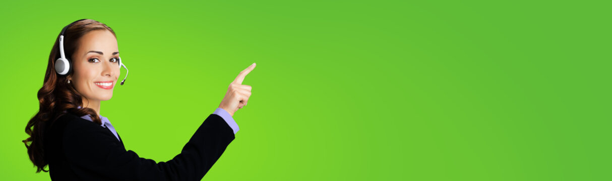 Call Center Service. Customer support or sales agent. Businesswoman or caller or phone operator in black suit showing pointing at copy space or imaginary. Green background. Help answering, consulting.