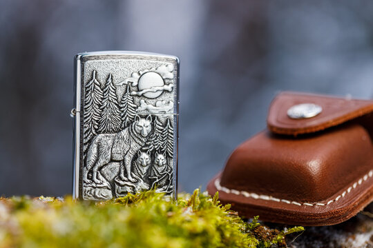 Vyborg, Russia - February 14, 2021: Zippo Timberwolves lighter and leather case on a mossy tree trunk in a winter forest close-up. The background is blurred.