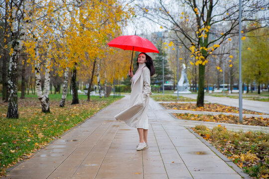woman in the park dancing under a red umbrella in the rain