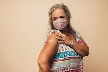 Fototapeta Woman showing her arm after getting vaccine obraz