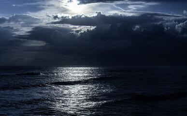 Zachód słońca nad oceanem i skalistym wybrzeżem.