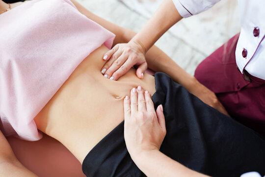Macro close up of therapist hands doing visceral massage on female abdomen.