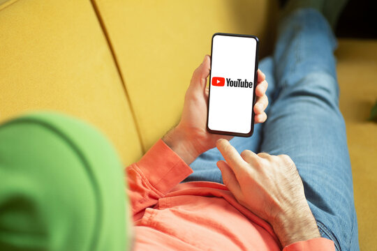 Youtube application in a smartphone screen in hand. Internet company and video service YouTube concept.
