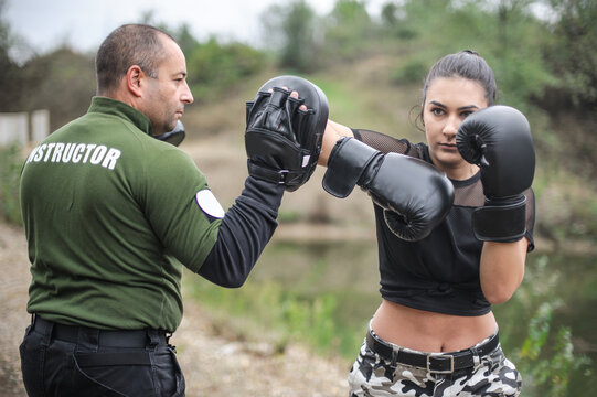 Sporty girl doing boxing exercises with trainer. Fitness outdoors workout. Strength, motivation, health and beauty