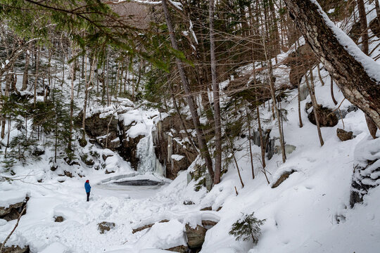 Hikers near frozen Kinsman Falls in Franconia Notch State Park during winter . New Hampshire mountains. USA
