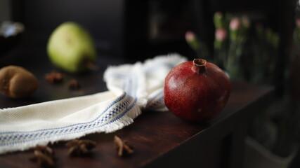 Obraz Granat owoc czerwony na stole drewnianym ciemnym - fototapety do salonu