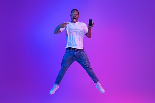 Amazed African Man Jumping Over Purple Neon Background And Pointing At Smartphone