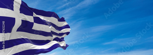 Large flag of Greece  waving in the wind against the sky with clouds on sunny day. 3d illustration