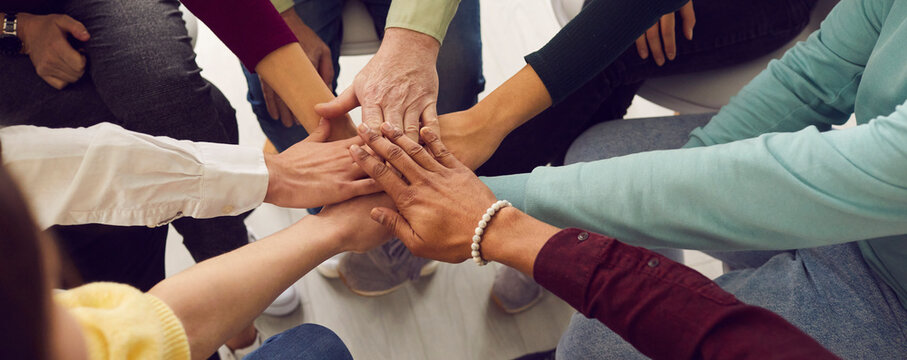 People of different ages and nationalities fold their hands on each other, symbolizing their unity and support. Team of people who are set up for productive work and a positive result. Close up.