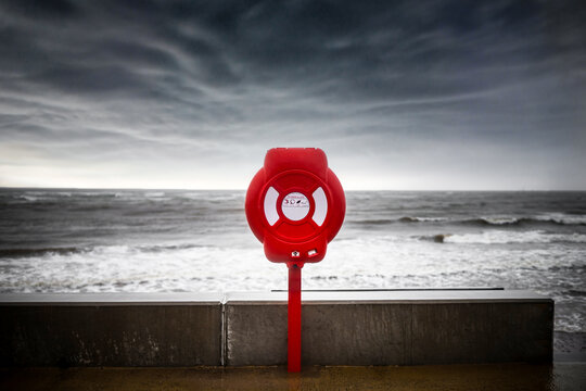 Bright red lifebuoy ring water rescue on stormy sea sky, big  ocean waves coastline. Life saving equipment belt preserver emergency station prevent drowning dramatic threatening storm