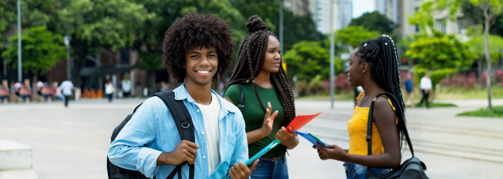 Young afro american male student with group of young adults