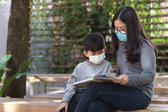 Asian boy with face mask reading the book with his mother