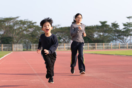Asian mother running with her son